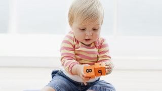 Kleinkind spielt mit Holzklötzen