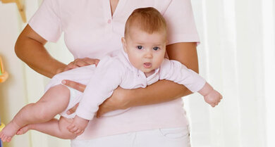 Fliegerstellung: Das Baby liegt auf dem Unterarm, die andere Hand stützt es ab