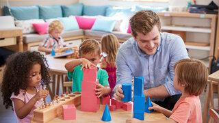 Lehrer und Schüler, die an Tischen in der Montessori-Schule arbeiten