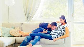 Mann liebkost den Bauch seiner schwangeren Frau