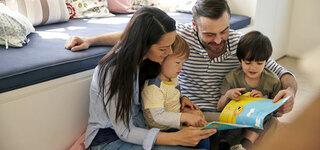 Familie liest in einem Buch