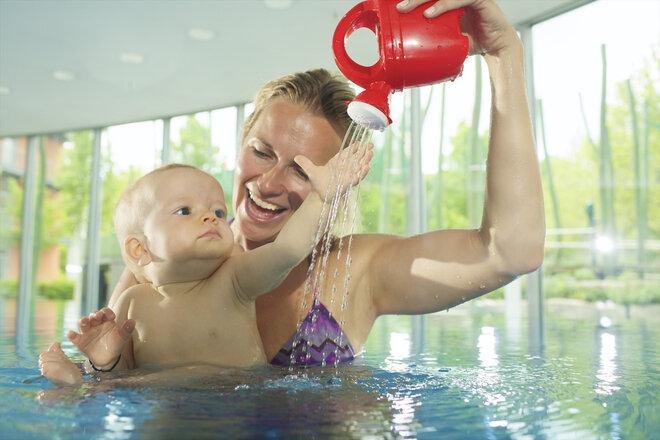 Mutter und Baby spielen mit Gießkanne im Wasser