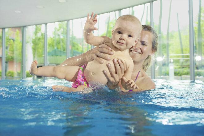Mutter wiegt ihr Baby im Wasser hin und her