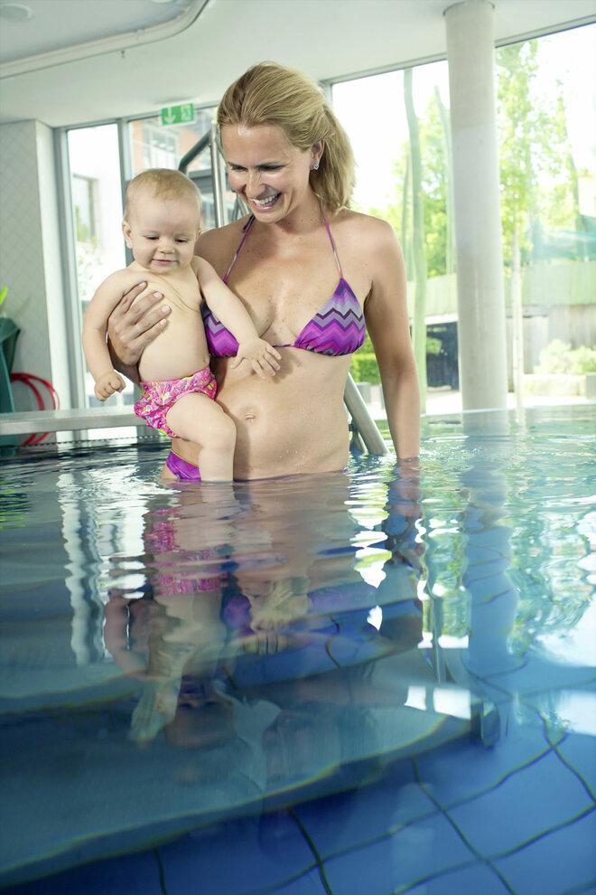 Mutter geht mit Baby langsam in das Wasser