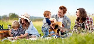 Patchworkfamilie macht Picknick auf einer Wiese