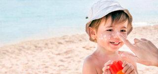 Kind wird mit Sonnenmilch eingecremt