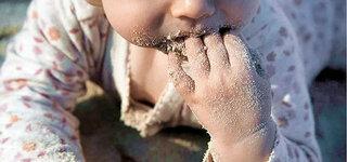 Baby isst Sand