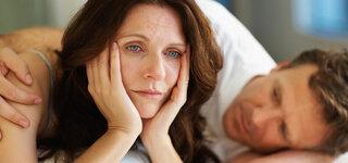 Mann tröstet Frau mit Postnataler Depression