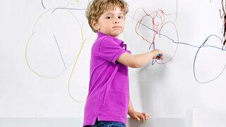 Junge malt Wand an