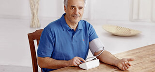 Mann misst zu Hause seinen Blutdruck