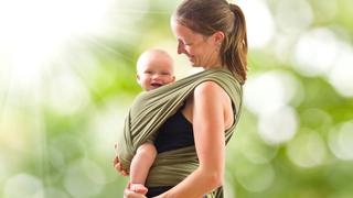 Frau trägt ihr Kleinkind im Tragtuch