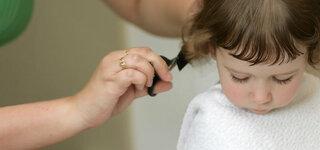 Mutter schneidt Kind die Haare