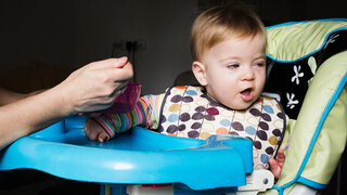 Baby, das von Erwachsenen im Hochstuhl gefüttert wird.