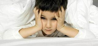 Kind mit Kopfschmerzen im Bett