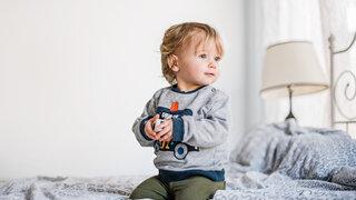 kleines Kind im Bett mit Spielzeug