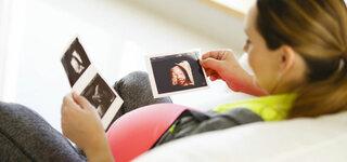 Frau schaut sich Ultraschallfotos an