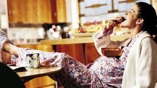 Schwangere Frau isst Pralinen in der Küche