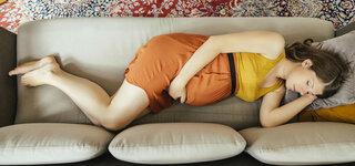 Schwangere Frau liegt auf Sofa