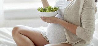 Schwangere Frau isst einen grünen Salat