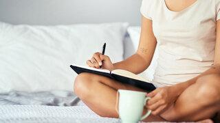 Frau sitzt auf dem Bett und schreibt in ein Notizbuch