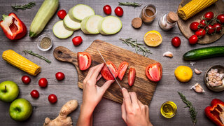 Hände schneiden Tomaten auf Brett mit Gemüse Obst
