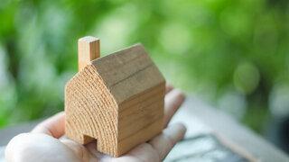 Hand hält Holzhaus