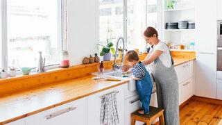 Mutter und Kleinkind in der Küche beim Abwaschen