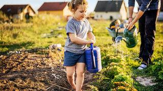 Mädchen mit der Gießkanne auf einem Gemüsefeld