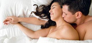 Paar liegt im Bett und kuschelt