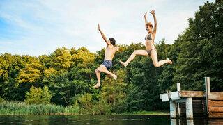 Paar springt vom Steg in einen See
