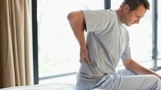 Mann auf Bett mit Rückenschmerzen