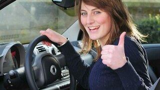 Frau im Auto zeigt sich zuversichtlich