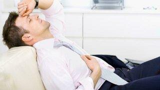 Mann liegt mit Kopfschmerzen auf dem Sofa