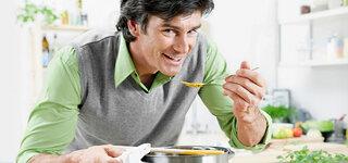 Mann schmeckt Suppe ab