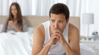 Schmerzen beim Sex: Mann sitzt enttäuscht und nachdenklich auf dem Bett