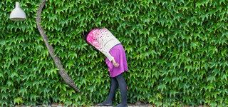 Frau steckt Kopf in Hecke