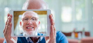 Senior fotografiert seine Driiten Zähne mit einem Tablet