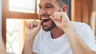 Mann reinigt Zähne mit Zahnseide
