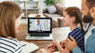 Familie schaut auf Computer mit Arzt auf dem Bildschirm
