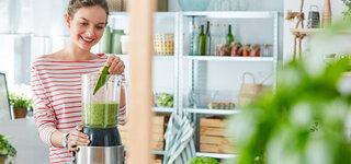 Junge Frau mixt sich einen grünen Smoothie