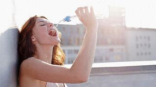 Frau trinkt aus Wasserflasche im Gebirge
