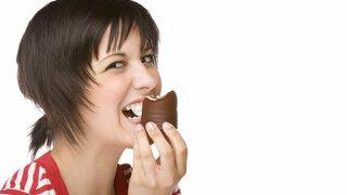 Frau isst Mohrenkopf