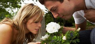 Mann und Frau riechen an Blume