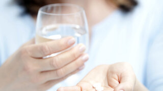 Frau nimmt Tabletten mit einem Glas Wasser ein