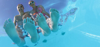Paar sitzt mit den Füßen im Wasser am Pool