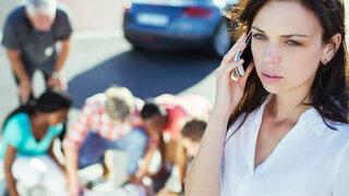 Erste Hilfe am Unfallort: Frau wählt den Notruf