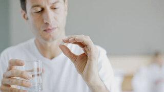 Mann nimmt Tablette mit Wasser ein