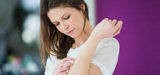 Junge Frau kratzt sich am Arm