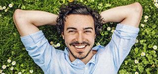 Lächelnder Mann liegt in der Wiese