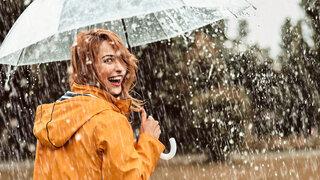 Fröhliche junge Frau mit Regenschirm und Regenmantel im Regen